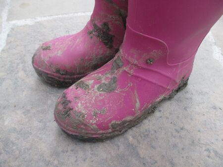 A childs muddy purple boots Stock Photo