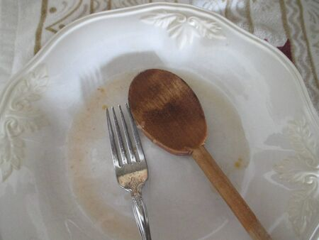 Wooden spoon and fork on a white plate Banco de Imagens