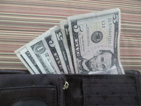 Five and one dollar bills in a womans wallet