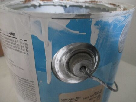 Dried white paint on a blue paint can