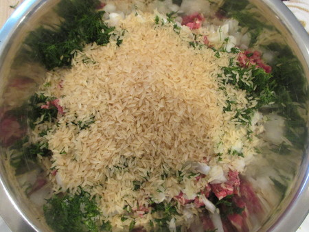 Uncooked white rice poured over a mixture of ground beef and chopped dill