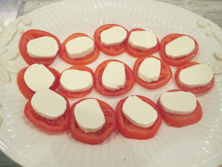 Sliced tomatoes with mozzarella cheese on a white platter