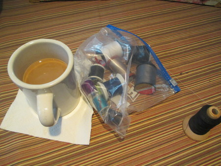 A cup of coffee and small spools of thread in a plastic bag Stockfoto
