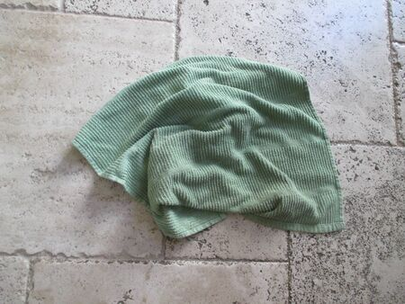 A small green towel on a tile floor Фото со стока