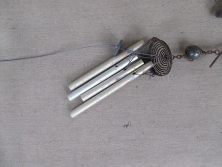 A small metal wind chime on a seat cushion Фото со стока