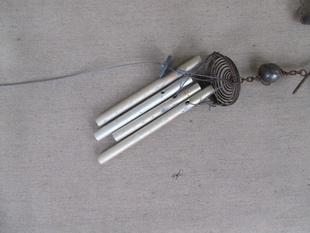 A small metal wind chime on a seat cushion Stockfoto