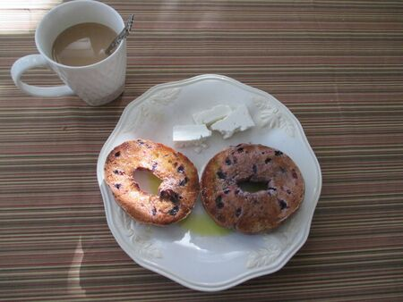 up of coffee and a blueberry bagel with olive oil and feta cheese