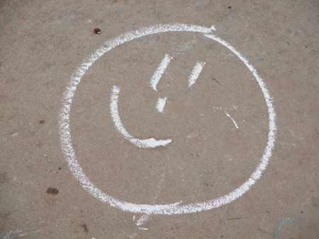white chalk drawing of a smiley face on a sidewalk