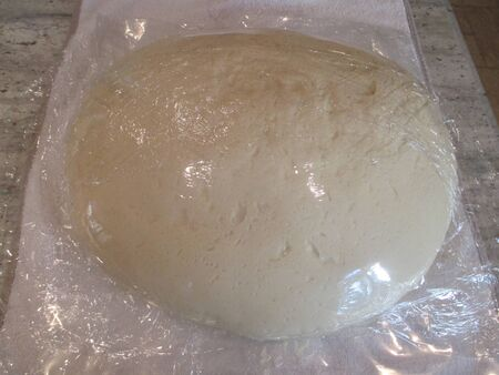 Bread dough wrapped in plastic wrap Stockfoto