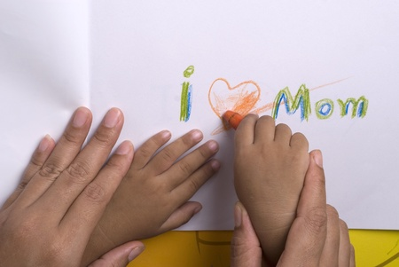 Mother helping her son for write his word  photo