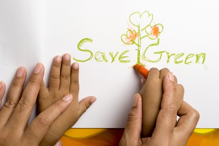 Mother helping her son for write the save green word  photo