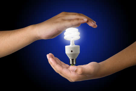 Energy saving lamp in hand with dark background. Energy saving concept. photo