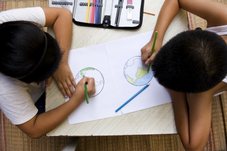 child drawing: Little boy and girl drawing an earth, Earth saving.