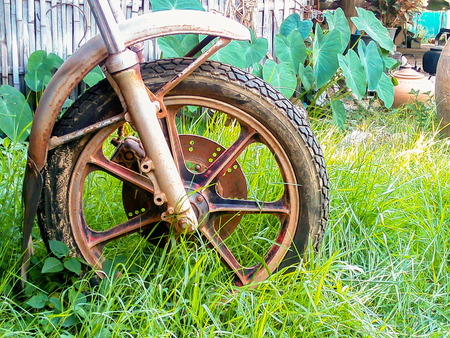classic art: Wheel motorbike old handmade. The image is not being left in the wilderness looked a classic art form. Stock Photo