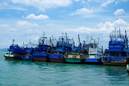 Row of blue fishing boats at pier against bluesky