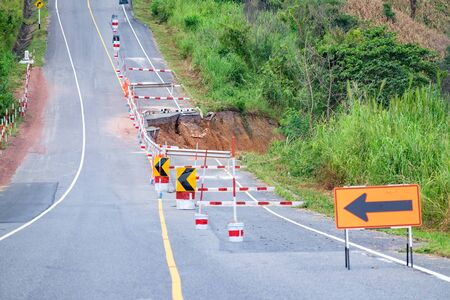 damaged: Damaged road with caution traffic sign Stock Photo