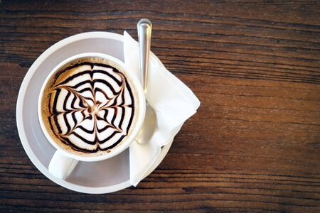 Mocha coffee (also called Caffe Mocha) with wooden saucer. Interior coffee shop. Main ingredients of mocha is chocolate, espresso, hot milk. (vintage tone)