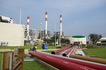 worker is fabricating pipe line with power plant background