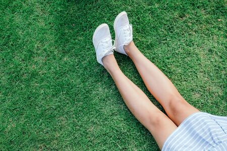 Legs in skirt and white slip-ons in the grass with copyspace. Selective focus and vintage tone