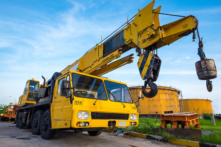 hydraulic lift: Yellow mobile crane against fuel oil storage tank area in power Stock Photo