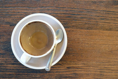 Empty coffee cup after drink on wood table in vintage tone