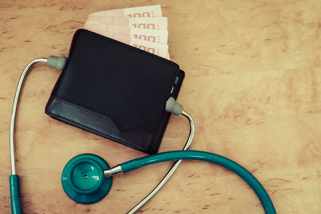 hecking an old wallet on a black table with a stethoscope. Stok Fotoğraf