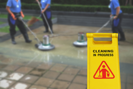 Cleaning in process and caution wet floor symbol againt cleaning blur background