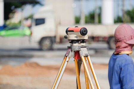 Surveyor equipment tacheometer or theodolite outdoors at construction road against worker blur background Stock Photo
