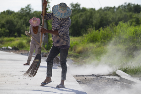 sweeper: Construction worker grouting dry sand with brush into paver bricks joints during road works Stock Photo