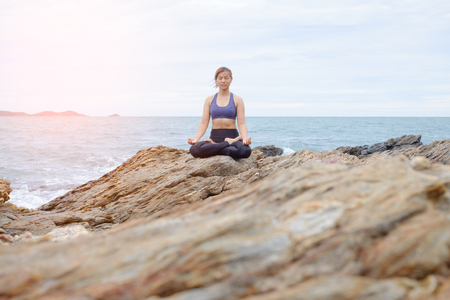 body consciousness: The woman practicing yoga on the beach at sunset. Stock Photo