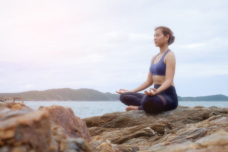 The woman practicing yoga on the beach at sunset. Stock Photo