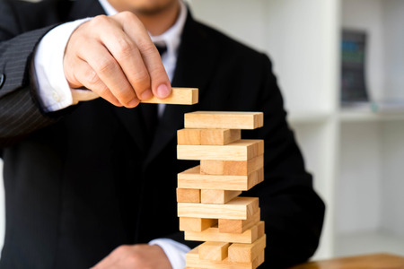 Businessmen picking dominoe blocks to fill the missing dominoes. Growing business concept.