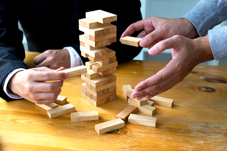 Businessmen picking domino blocks to fill the missing dominos and protect domino to fail. Growing business concept.
