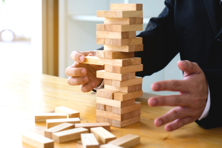 Businessmen picking dominoe blocks to fill the missing dominos and protect domino to fail. Growing business concept.