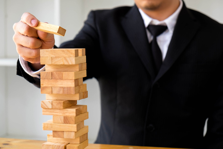 Businessmen picking blocks to fill the missing dominos. Growing business concept. Stock Photo