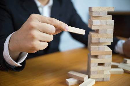 Businessmen picking wood blocks to fill the missing . Growing business concept.