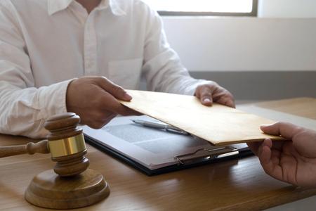 De advocaat verzendt contractdocumenten naar cliënt in bureau. adviseur advocaat, advocaat, rechter, concept. Stockfoto