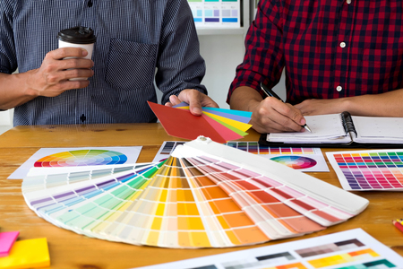 Graphic designers choose colors from the color bands samples for design .Designer graphic creativity working concept . Stock Photo
