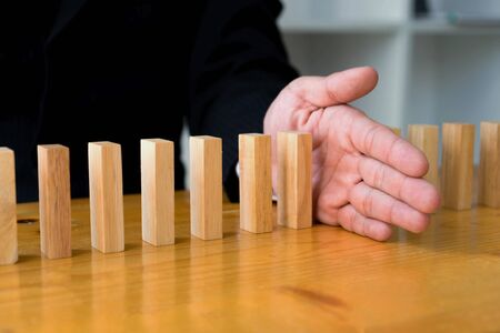Business hand stops domino continuous overturned meaning that hindered business failure. Stop over this business failure concept.