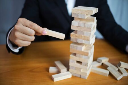 Businessmen picking wood blocks to fill the missing dominoes. Growing business concept.