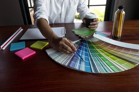 Graphic designer choose colors from the color bands samples for design .Designer graphic creativity working concept.
