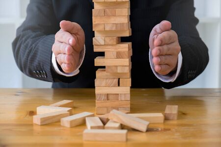 Businessmen protect domino to fail. Growing business concept. Stock fotó