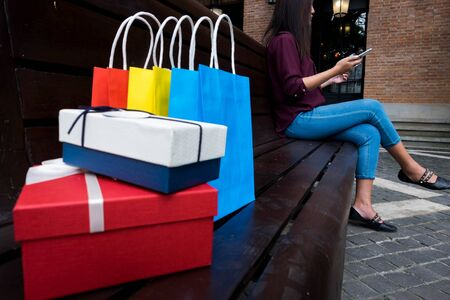 Woman holding credit card and using smartphone for shopping online in shopping mall.