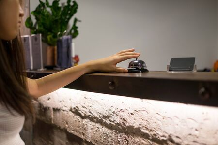 Close up women call hotel reception on counter desk with finger push a bell in lobby hotel. hotel concept.