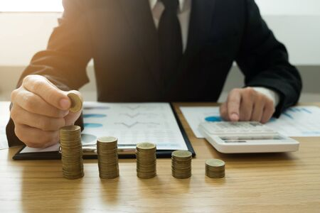 Businessman picks coins on the table, counts money . Business concept. Stock fotó