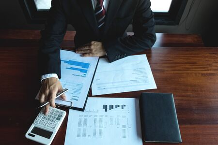 Businessman working with income statement document on the wood table.