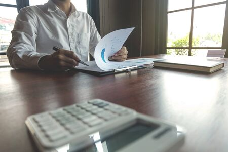 Businessman working with income statement document on the wood table.Business concept. Stock fotó