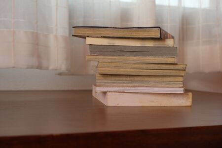 Close up of stack or pile of old book that place on a table near to the window and curtain with blurred background Foto de archivo