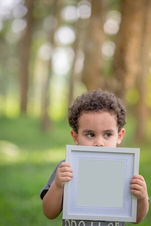 Boy standing holding a white frame under a tree and pasture.