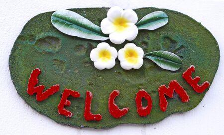 welcome sign: Signe de bienvenue sur le fond blanc avec des fleurs franjipani c�ramique